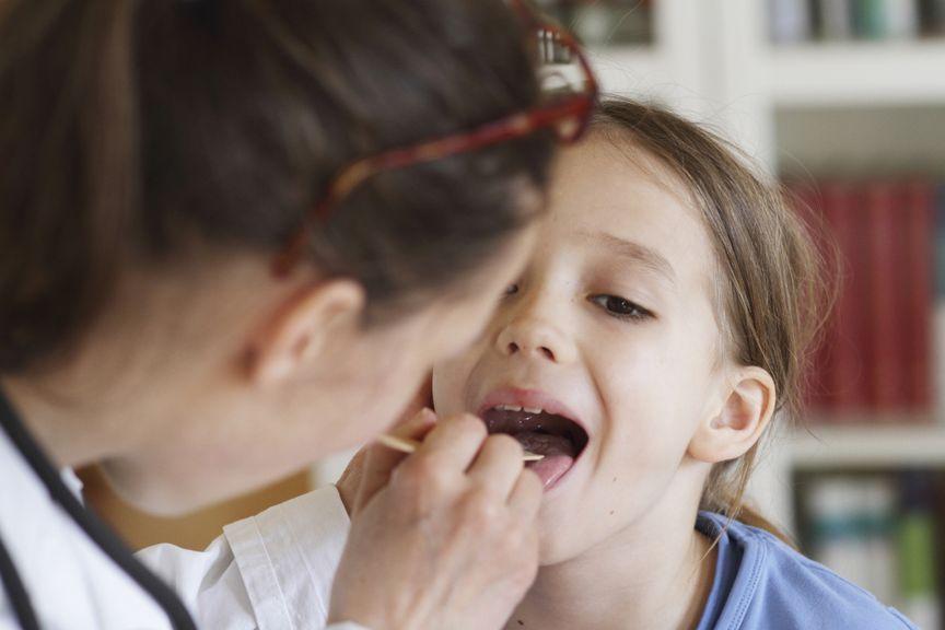 Ärztin untersucht den Mund eines Mädchens