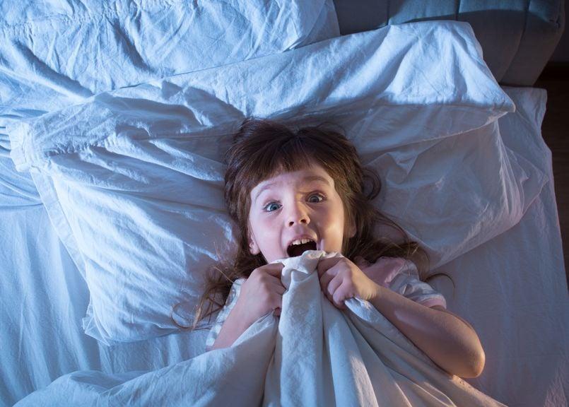 Mädchen liegt im Bett und schreit vor Schreck