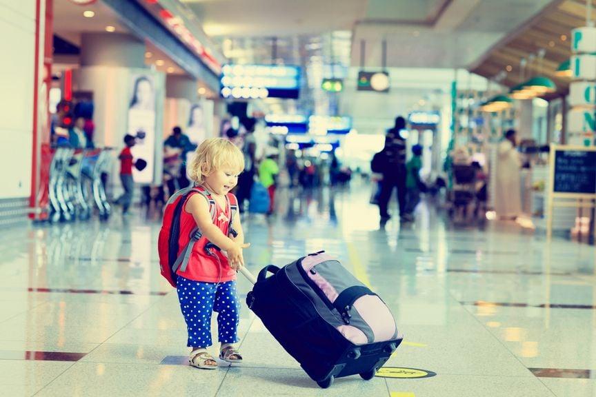 Kind mit Koffer in der Flughalle