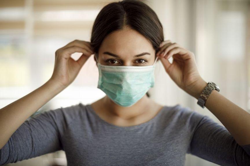 Frau zieht Gesichtsmaske an