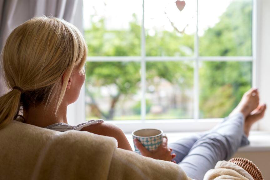 Frau sitzt vor dem Fenster, Beine hoch, mit Becher