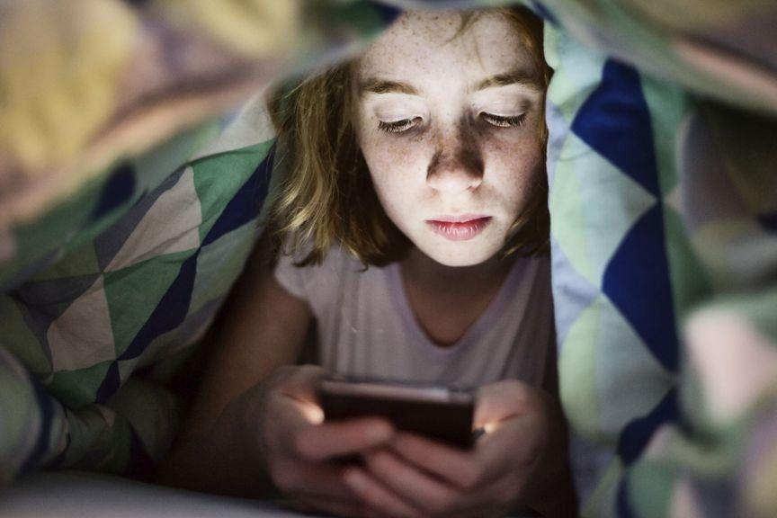 Kind mit Smartphone im Bett