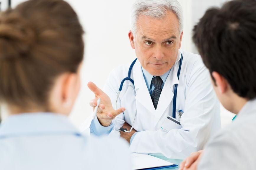 Paar, von hinten, in der medizinischen Beratung mit Arzt