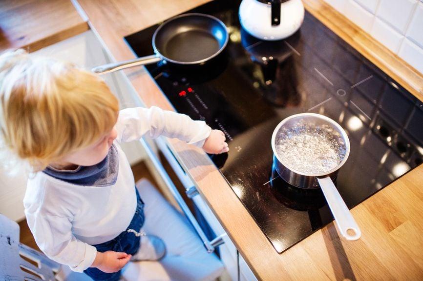 Kind steht am Kochherd mit kochendem Wasser