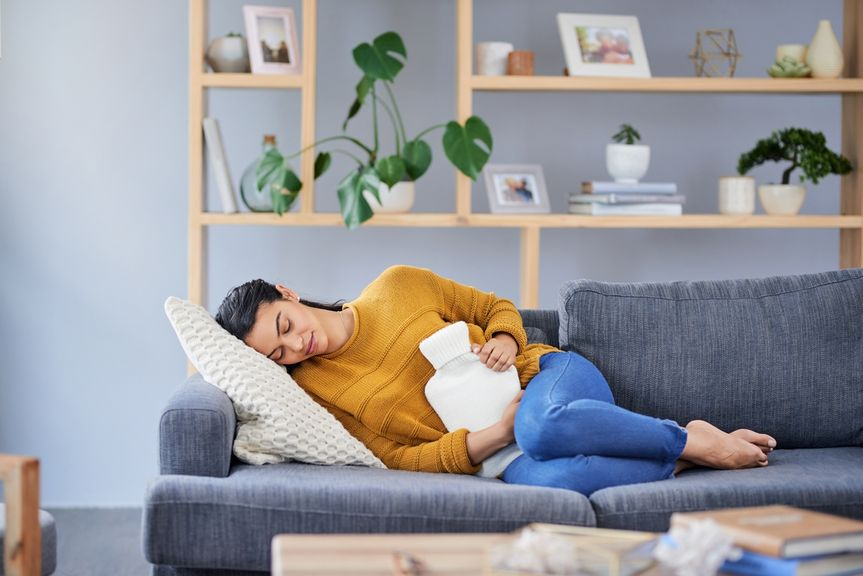 Frau liegt auf dem Sofa mit einer Wärmflasche auf dem Bauch