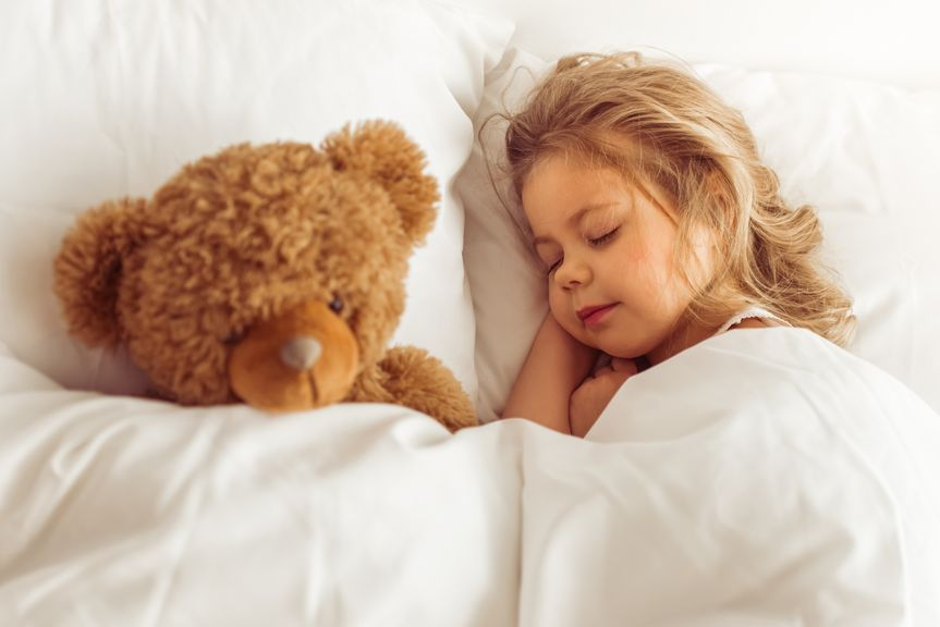 Mädchen schläft mit ihrem Teddy im Bett