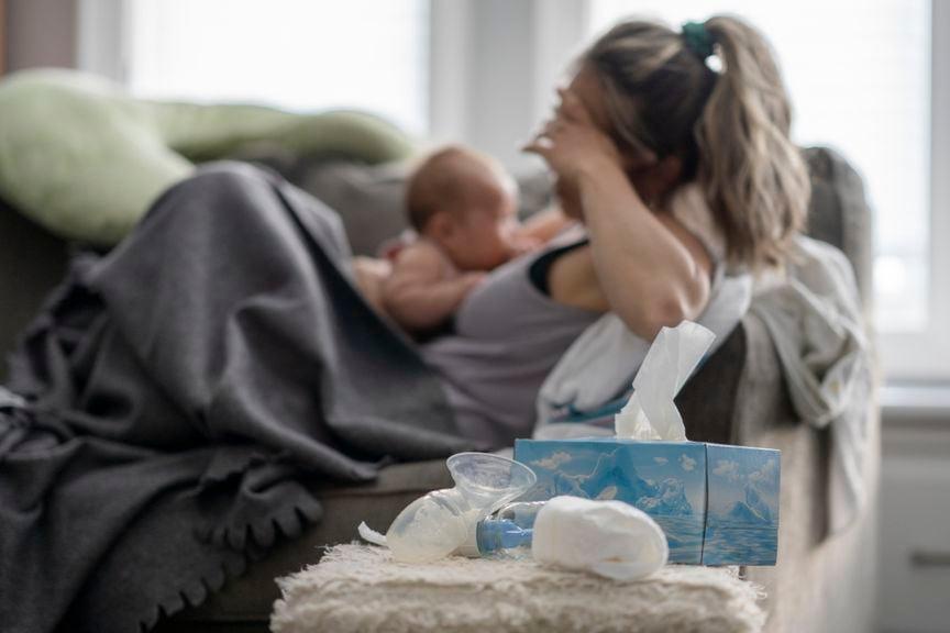 Verzweifelte Mutter mit Baby auf dem Sofa