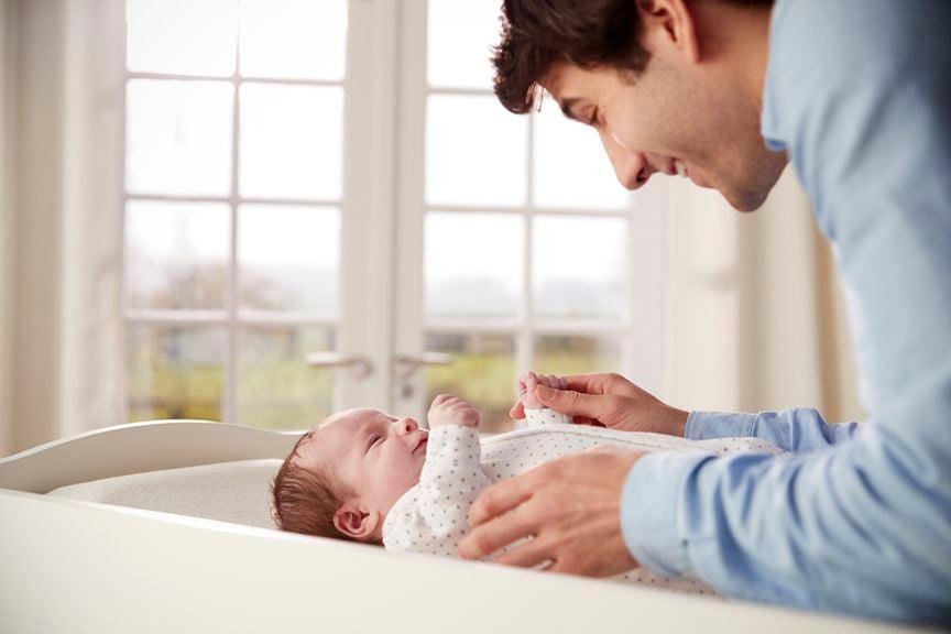 Vater wickelt Baby auf dem Wickeltisch