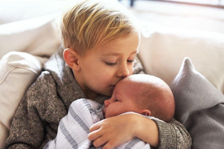 Grosser Bruder hält sein neugeborenes Geschwister im Arm und küsst es