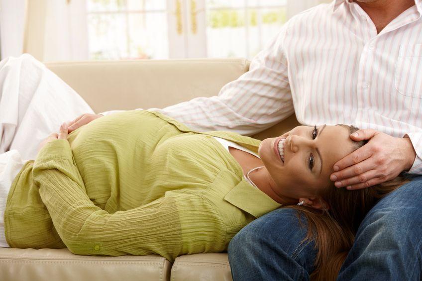 Schwangere liegt auf dem Schoss vom Partner