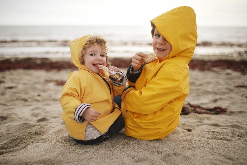 Geschwister in gelben Regenmänteln am Strand