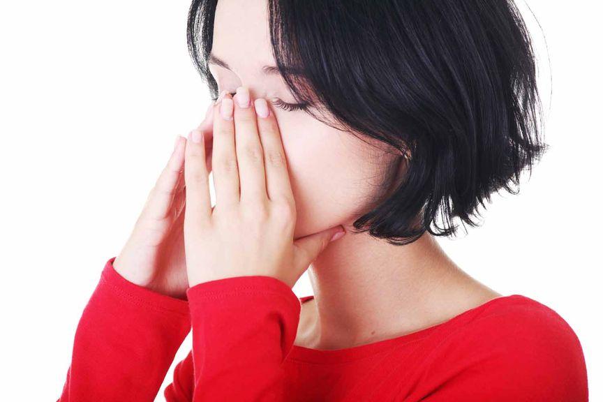 Frau reibt sich den Nasenrücken