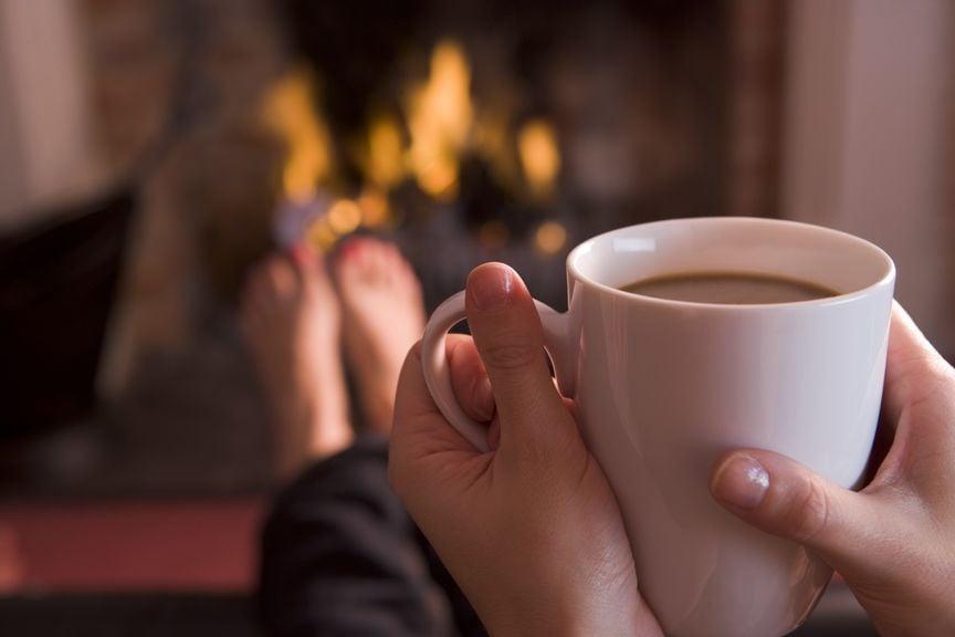 Tasse mit warmem Getränk in der Hand am Cheminée