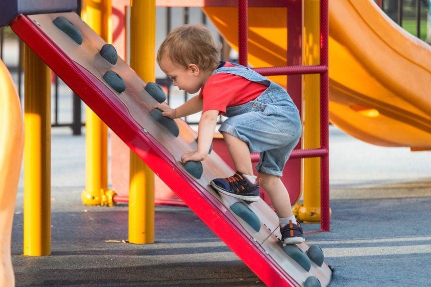Kleiner Junge klettert auf ein Spielgerät auf dem Spielplatz