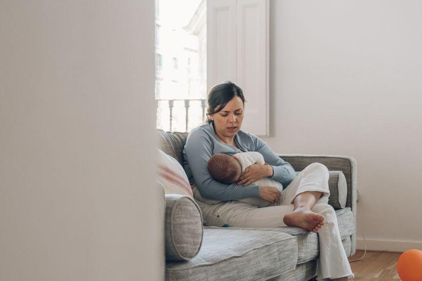 Mutter stillt ihr Baby auf dem Sofa