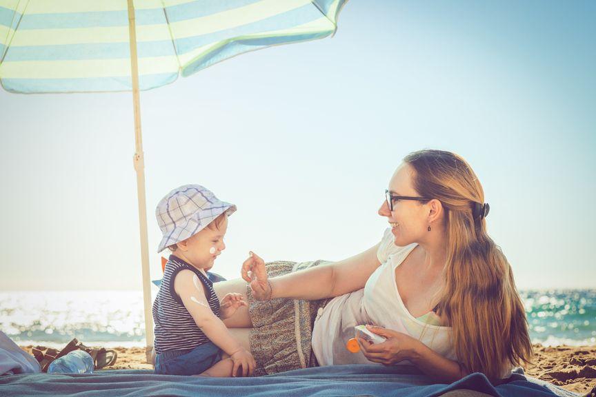 Mutter liegt mit Baby am Strand unter Sonnenschirm