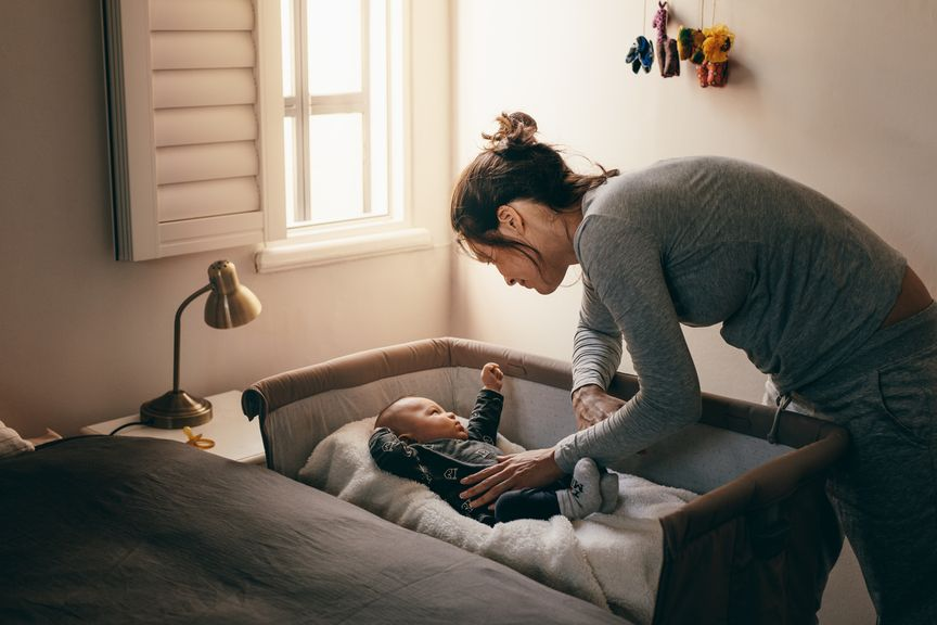Mutter bringt Baby ins Bett