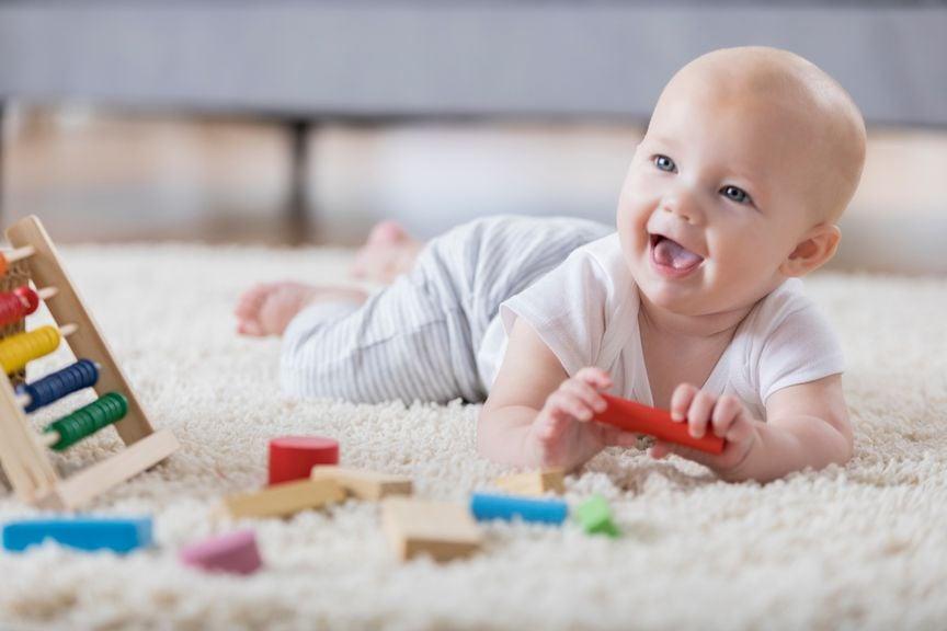 Baby liegt auf dem Bauch, spielt und lächelt