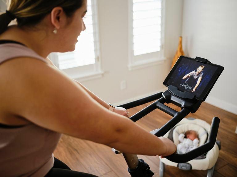 Mutter mit Säugling im Maxicosi trainiert auf dem Velo