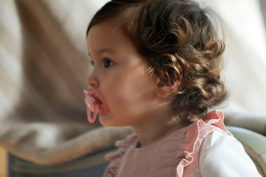 Kind mit Nuggi im Mund