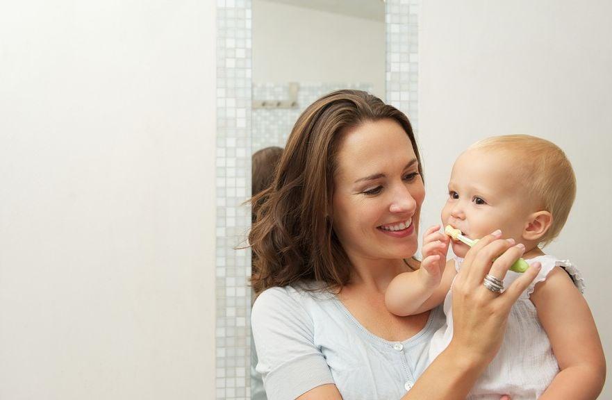 Mutter putzt Baby die Zähne