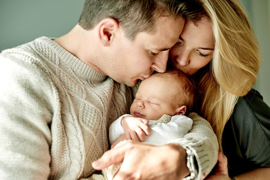 Paar hält schlafenden Säugling im Arm und küsst