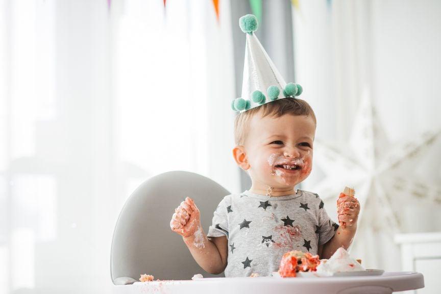 Baby mit Partyhut und verschmierten Händen und Mund