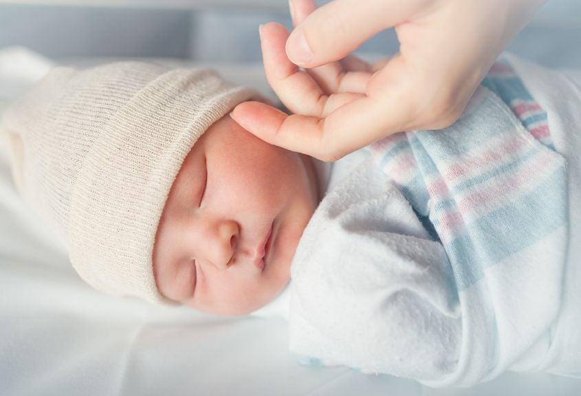 Hand der Mutter streicht über die Wange ihres Neugeborenen