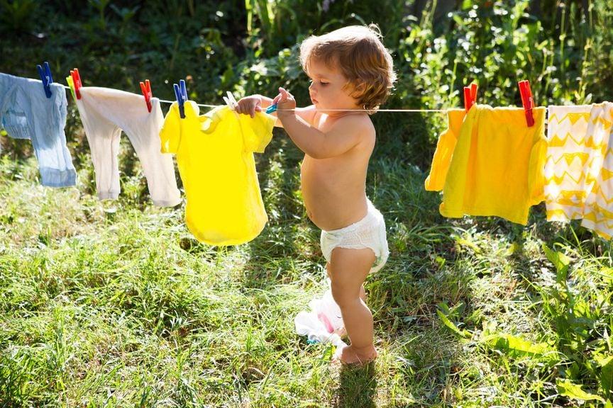 Kind hängt im Garten Kinderwäsche auf die Leine