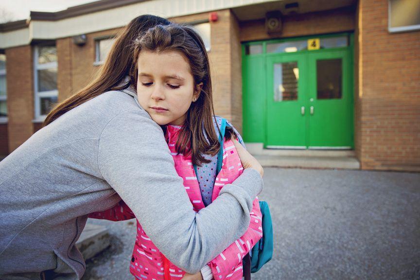 Schulkind nimmt mit ängstlichem Blick Abschied von der Mutter
