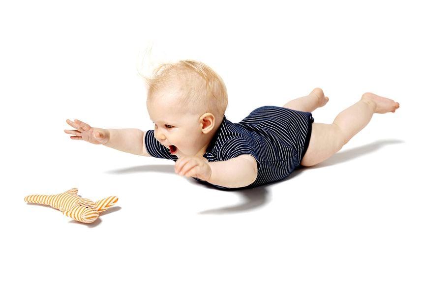 Baby liegt auf dem Bauch, streckt Hände und Beine in die Luft