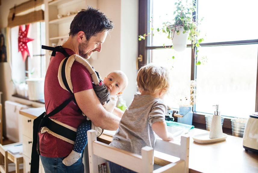 Vater mit Baby und Kind zu Hause beim Abwasch