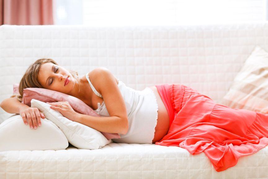 Schwangere liegt auf dem Sofa