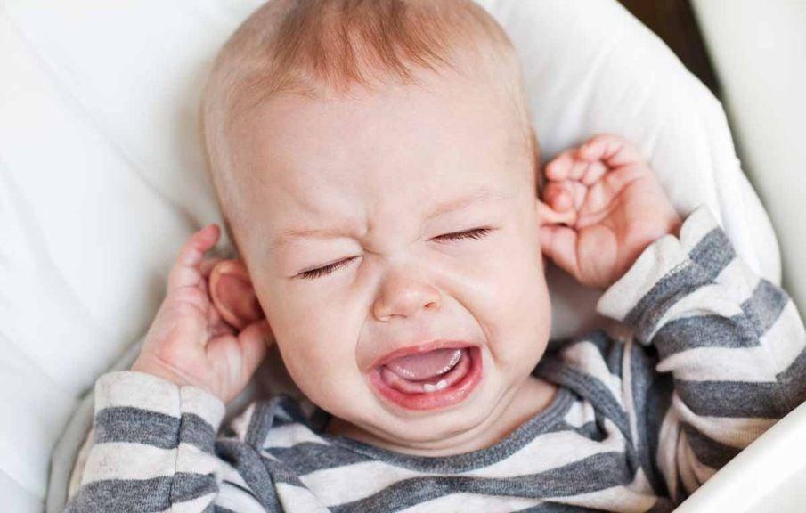 Baby weint und zieht an den Ohren