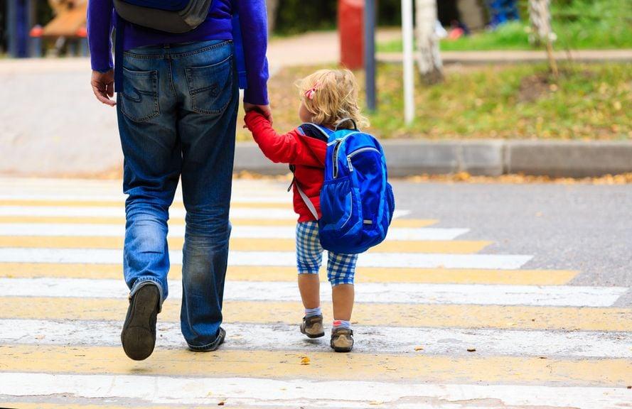 Vater geht mit Kind über den Fussgängerstreifen