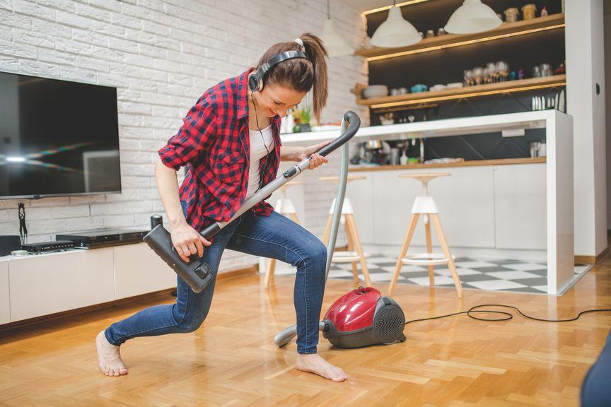 Frau tanzt mit Staubsauger bei der Hausarbeit