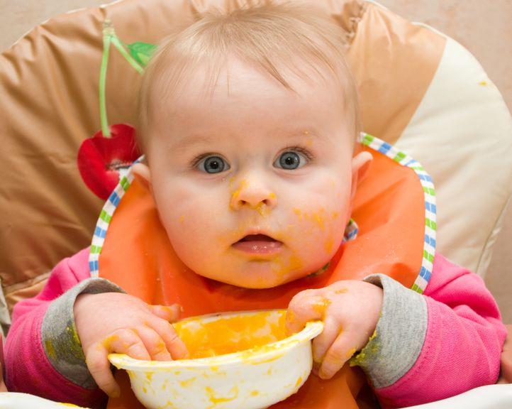 Baby mit Breischüssel und Latz isst mit den Fingern