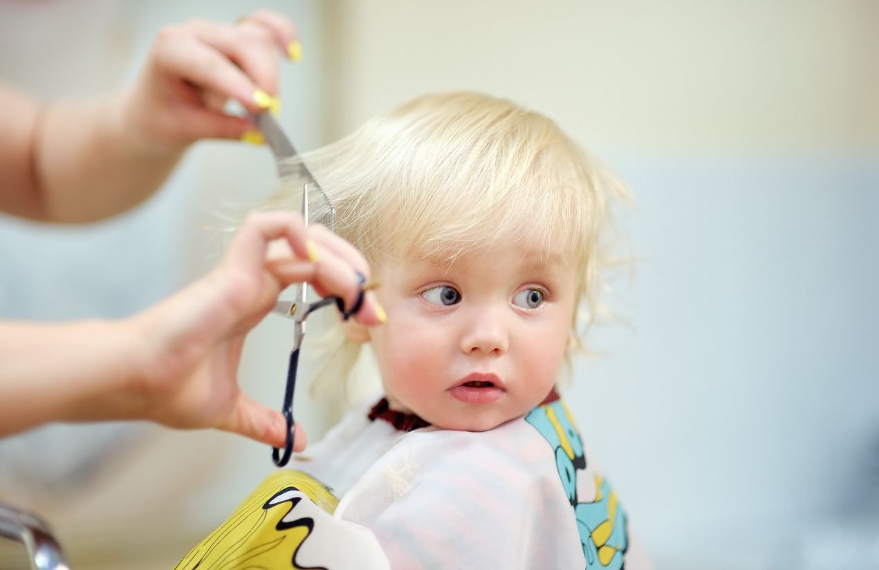 Kind bekommt den ersten Haarschnitt