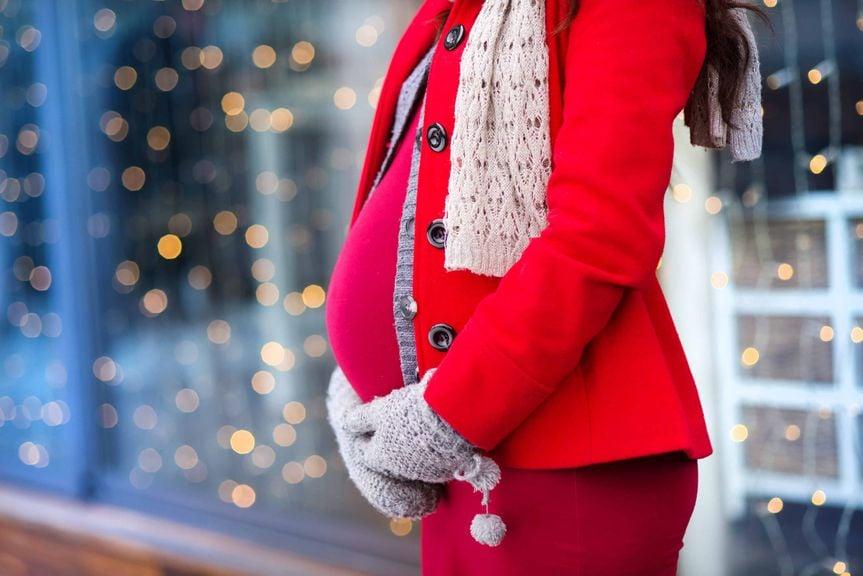 Schwangere wartet vor einem Schaufenster