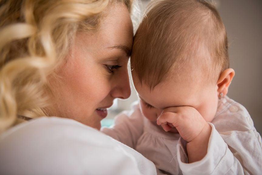 Mutter mit Baby, das sich die Augen reibt