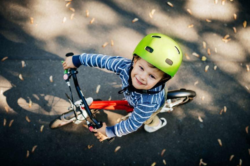 Kind mit Helm auf Velo