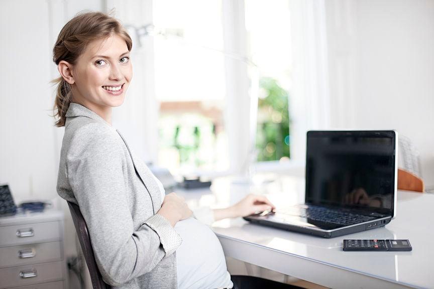 Schwangere sitzt am Schreibtisch mit Laptop