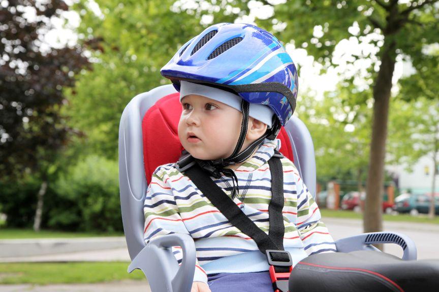 Kind mit einem Helm im Velositz