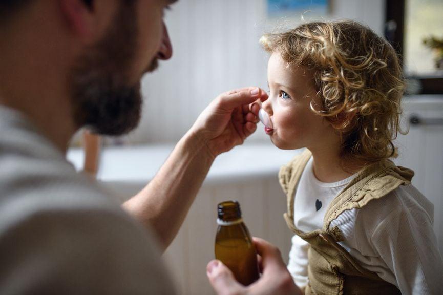Vater gibt seinem Kind einen Medikamentensaft