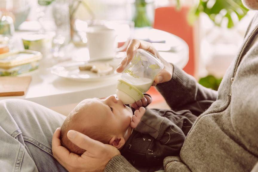 Vater füttert Baby mit Schoppen