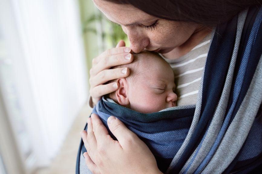 Mutter trägt Baby im Tragetuch und küsst es auf den Kopf