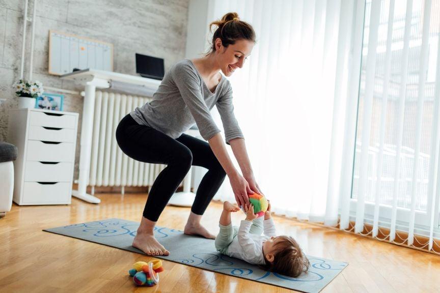 Mutter macht Sport, Baby liegt dabei auf dem Boden