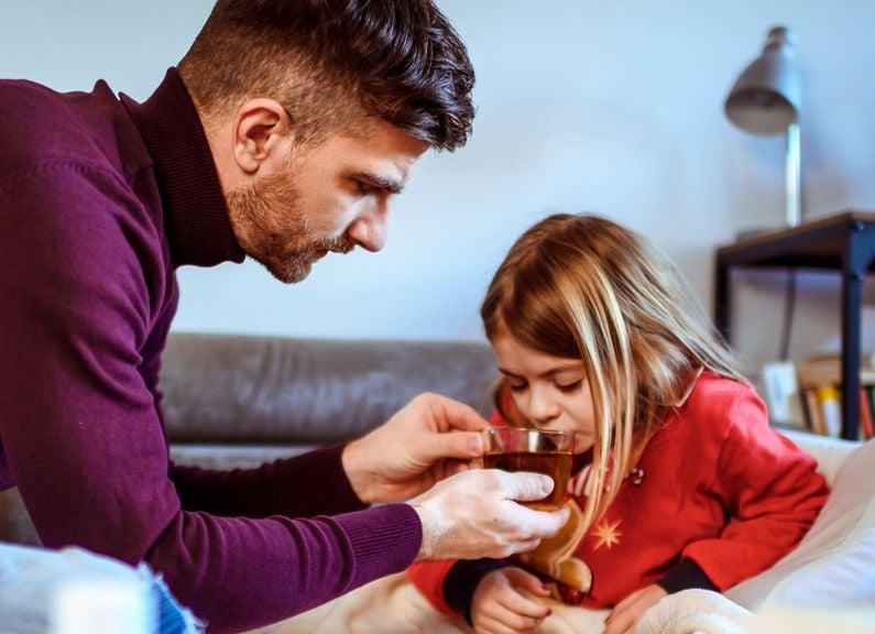Vater gibt seiner kranken Tochter zu trinken