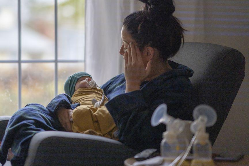 Müde Mutter mit Neugeborenem und Milchpumpe
