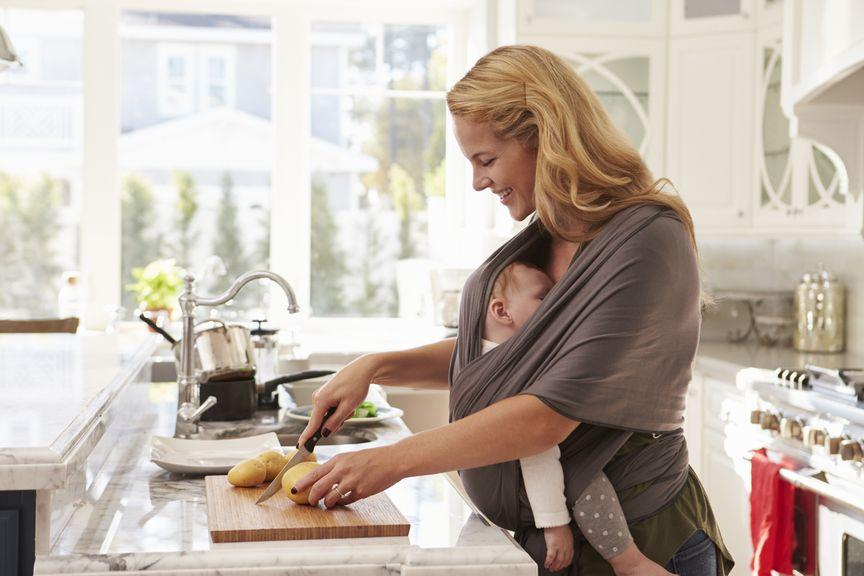 Mutter mit schlafendem Baby im Tragetuch am kochen